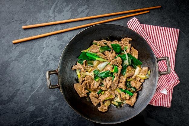 Tradicional chinesa mongol carne stir fry em chinês wok ferro fundido com pauzinhos de cozinha