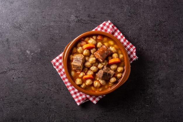 Tradicional cocido madrileão espanhol em tigela sobre fundo preto rústico