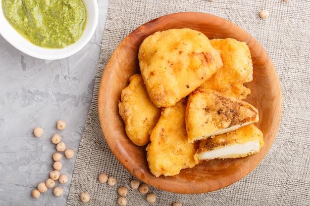 Tradicional comida indiana paneer pakora em placa de madeira com chutney de hortelã