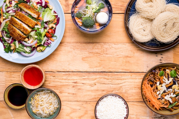 Tradicional comida tailandesa, incluindo sopa de legumes fritos salada de peixe e arroz vermicelli na mesa de madeira