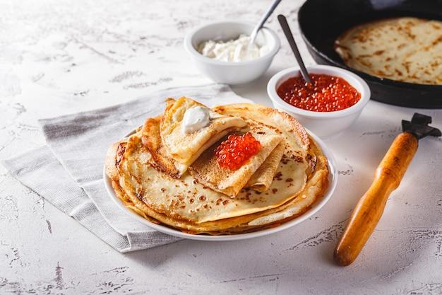 Tradicional crepes russos blini empilhados em um prato com caviar vermelho e creme de leite fresco. refeição tradicional do festival russo de maslenitsa. comida russa, cozinha russa