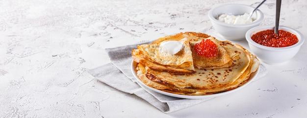 Tradicional crepes russos blini empilhados em um prato com caviar vermelho e creme de leite fresco. refeição tradicional do festival russo de maslenitsa.