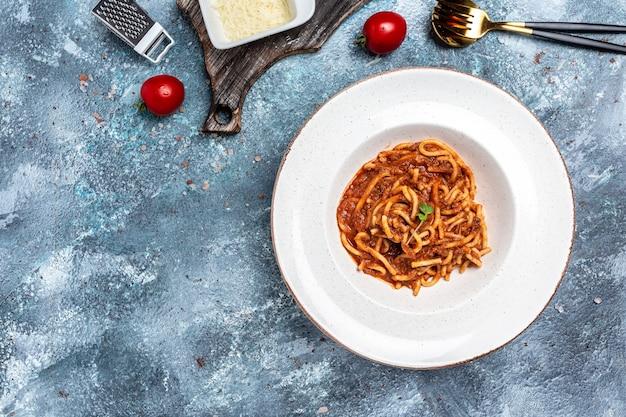 Tradicional espaguete italiano à bolonhesa com molho de tomate e carne picada servido em um prato com queijo parmesão. banner, menu, local de receita para texto, vista superior.