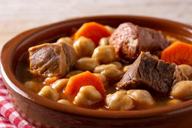 Tradicional espanhol cocido madrileño em tigela na mesa de madeira rústica.