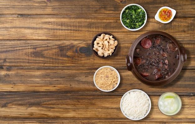 Tradicional feijoada brasileira com arroz, couve, caipirinha, torresmo, farinha de mandioca e copa