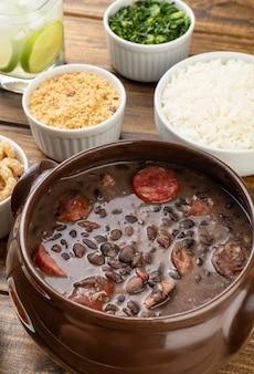 Tradicional feijoada brasileira com arroz, couve, farinha de mandioca e caipirinha.