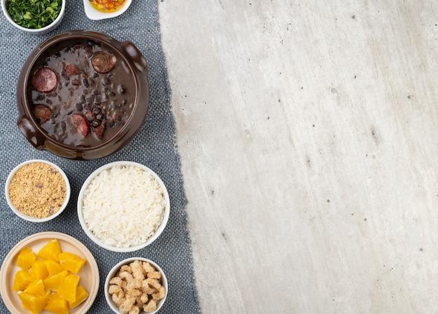 Tradicional feijoada brasileira com arroz, couve, laranja, torresmo, farinha de mandioca e copa.
