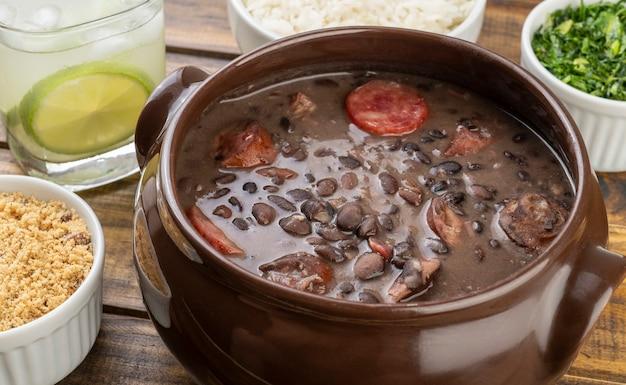 Tradicional feijoada brasileira com couve, arroz, farinha de mandioca e caipirinha.