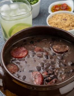 Tradicional feijoada brasileira com couve, pimenta, farinha de mandioca e caipirinha.