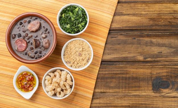 Tradicional feijoada brasileira com farinha de mandioca, couve, caipirinha e copinha.