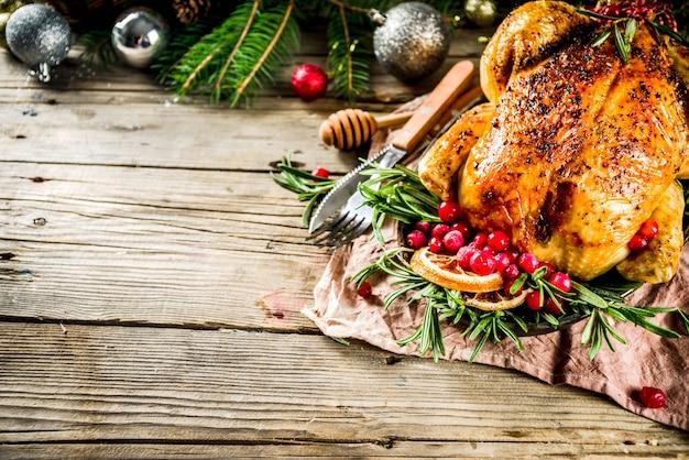 Tradicional frango assado no natal e no dia de ação de graças com frutas e alecrim. mesa de natal de madeira rústica, com galhos de árvores de natal e espaço de cópia de decorações