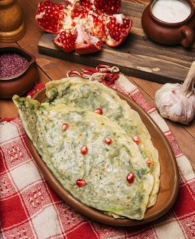 Tradicional gutab vegetal caucasiano, kutab, gozleme com sumakh, granate sementes e iogurte na placa de madeira