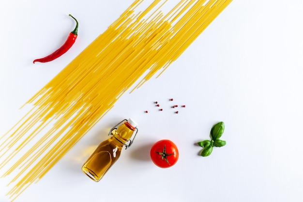 Tradicional macarrão italiano espaguete, tomate cereja, manjericão, azeite e pimenta malagueta. vista superior, close-up, copie o espaço no fundo branco