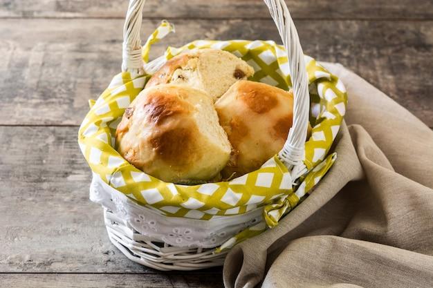 Tradicional páscoa quente cruz pães em uma cesta na mesa de madeira