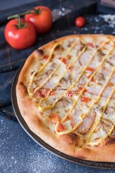 Tradicional pizza italiana com frango, presunto na mesa de pedra azul escuro