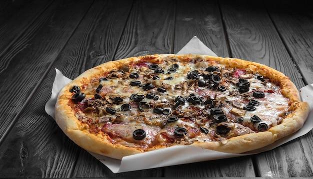 Tradicional pizza italiana em tábua de madeira preta escura