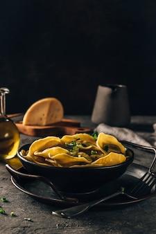 Tradicional ravióli italiano recheado com queijo em prato preto com foco seletivo de fundo escuro