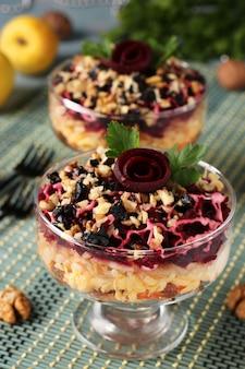 Tradicional salada russa com queijo, beterraba e cenoura, decorada com rosas de beterraba, nozes e ameixas secas, em porções.