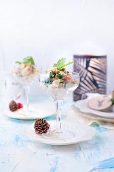 Tradicional salada russa de legumes e carne, com maionese. servido em um copo e decorado com salsa, em uma mesa branca