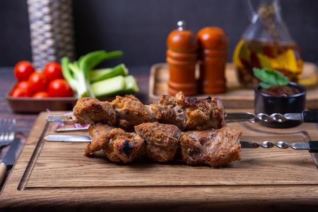 Tradicional shashlik russo em espetos com legumes. carne de porco grelhada (shish kebab). fechar-se.