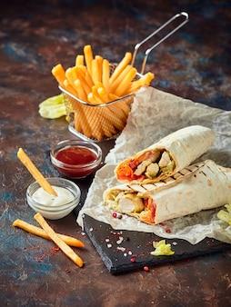 Tradicional shawarma oriental com frango e vegetais e batata frita com molhos na ardósia. comida rápida. comida oriental.