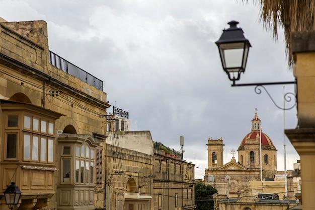 Tradicional, varanda de madeira e fachada de pedra, típico para arquitetura de gozo, malta