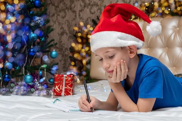 Tradições de ano novo e natal. um menino caucasiano com um chapéu de papai noel vermelho escrevendo uma carta para o papai noel em casa