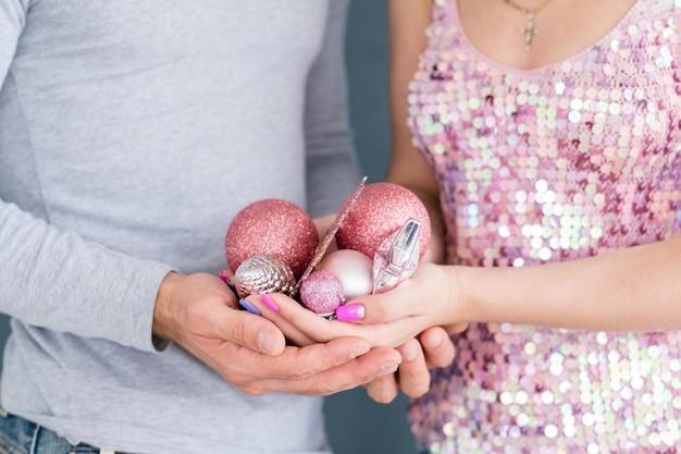 Tradições de decoração de casa de natal em família. homem e mulher segurando bolas brilhantes de ouro rosa e brinquedos nas mãos