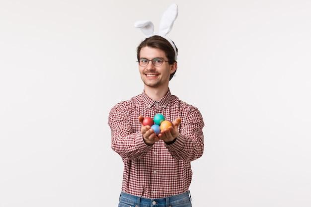 Tradições, feriados religiosos, conceito de celebração. feliz tipo e bonito homem europeu em orelhas de coelho, óculos, dando ovos pintados para o dia de páscoa, sorrindo comovente, carrinho