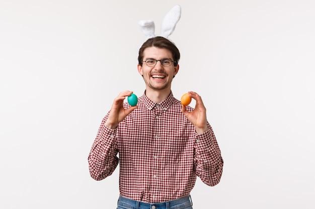 Tradições, feriados religiosos, conceito de celebração homem caucasiano barbudo engraçado e fofo passa tempo com a família durante o dia de páscoa, usa orelhas de coelho, segurando dois ovos pintados e sorrindo com alegria