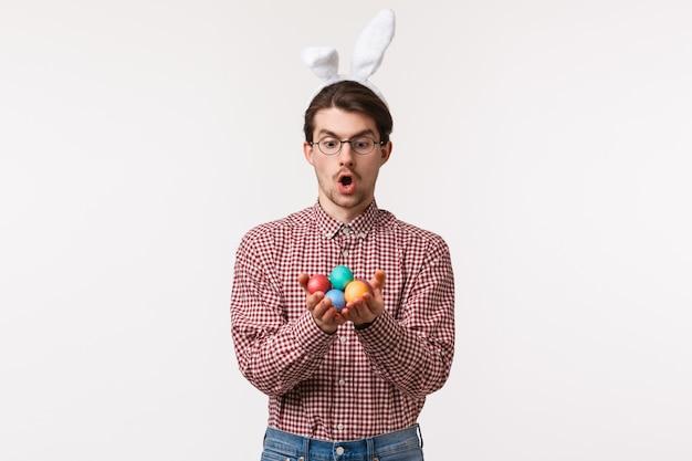 Tradições, feriados religiosos, conceito de celebração. jovem caucasiano divertido e animado em orelhas de coelho, óculos, boca aberta espantado, segurando ovos pintados comemorando o dia de páscoa