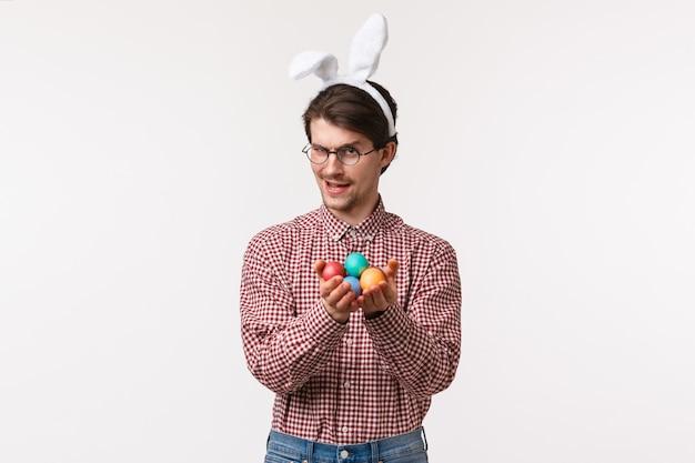 Tradições, feriados religiosos, conceito de celebração sassy e manhoso bonito caucasiano em copos com orelhas de coelho, dando ovos pintados e olhando a câmera astuta, insinuando,