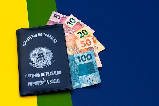 Tradução república federativa do brasil, ministério do trabalho. carteira de trabalho brasileira. cédulas brasileiras. plano de fundo representando a bandeira do brasil.