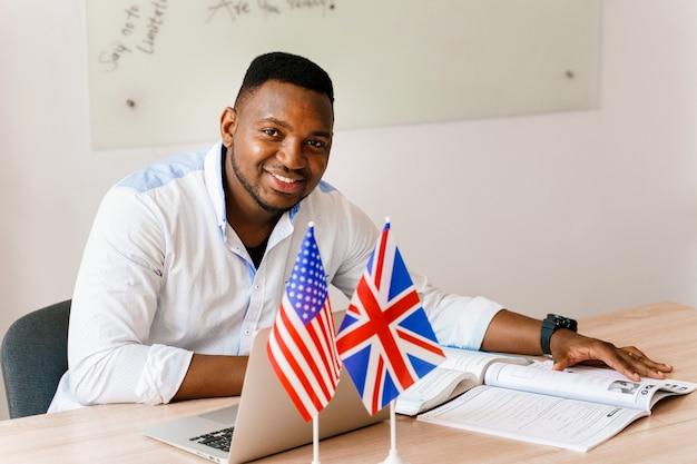 Tradutor negro bonito usa seu laptop para trabalho online de acordo com o distanciamento social