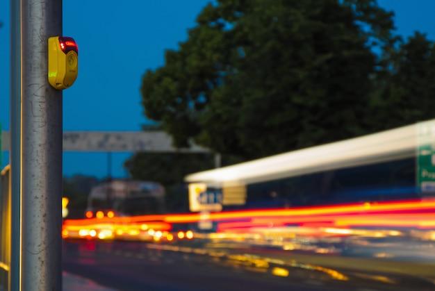Tráfego da cidade à noite, espera botão faixa de pedestres fechar amarelo e carros luzes