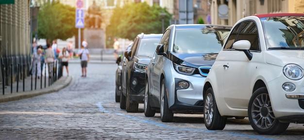 Tráfego da cidade com carros estacionados em fila do lado da rua.