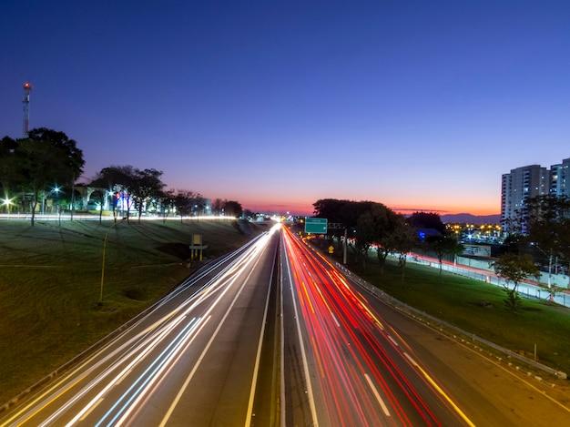 Tráfego de veículos na rodovia no início da noite.