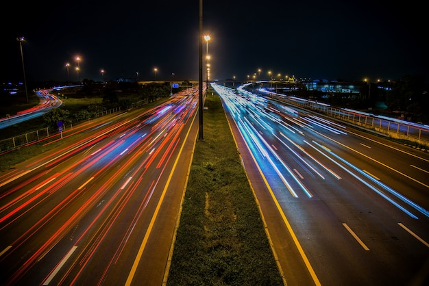 Tráfego de velocidade - trilhas leves na auto-estrada da estrada à noite, longa exposição