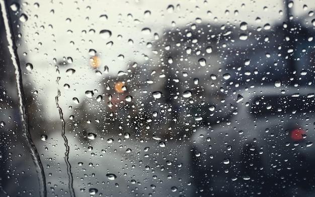 Tráfego matinal em dia chuvoso, vista através do pára-brisa durante a tempestade de chuva com foco seletivo.