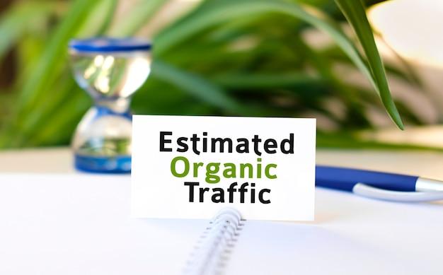 Tráfego orgânico estimado - texto de conceito de negócio em um caderno branco e um relógio de ampulheta, folhas verdes de flores