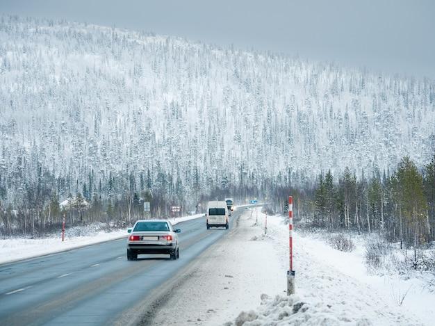 Tráfego polar de carros em uma estrada escorregadia entre colinas cobertas de neve. rússia.