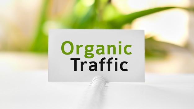 Tráfego seo orgânico - texto de conceito de negócios seo em um caderno branco e flores verdes