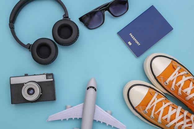 Trafel flat lay. fones de ouvido estéreo, tênis e acessórios de viagem sobre fundo azul. vista do topo. copie o espaço