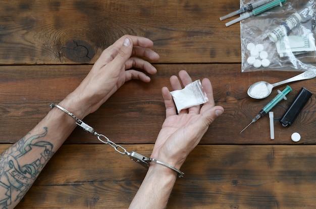 Traficantes de drogas foram presos juntamente com sua heroína. polícia prende traficante de drogas com algemas