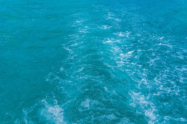 Trail na superfície da água do mar por trás do barco