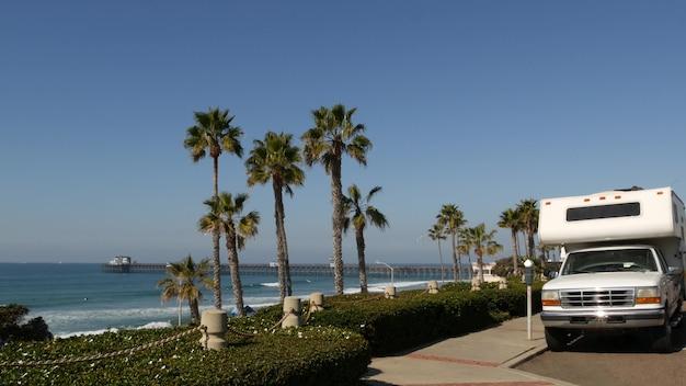 Trailer de motorhome ou caravana para viagem. palmeiras tropicais à beira-mar e praia do oceano pacífico, oceanside califórnia eua. férias à beira-mar em uma van, trailer rv. autocaravana.