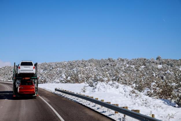 Trailer transporta carros na estrada na estrada de inverno com paisagem de neve
