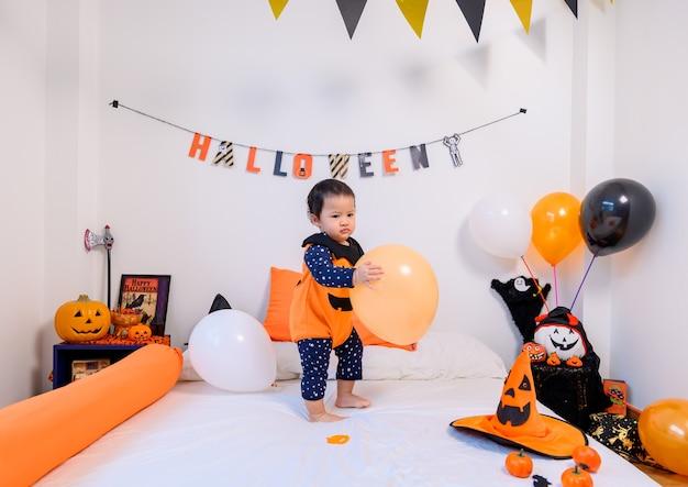 Traje de criança para o festival de halloween em casa. celebração da família da decoração do quarto no outono e no outono.
