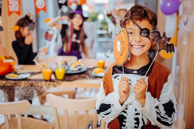Traje de pirata. aluna de cabelos escuros usando fantasia de pirata no halloween e animada enquanto se diverte com os amigos