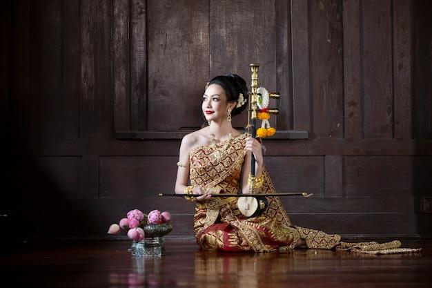 Traje tradicional de mulheres tailandesas sentado em uma casa de madeira.